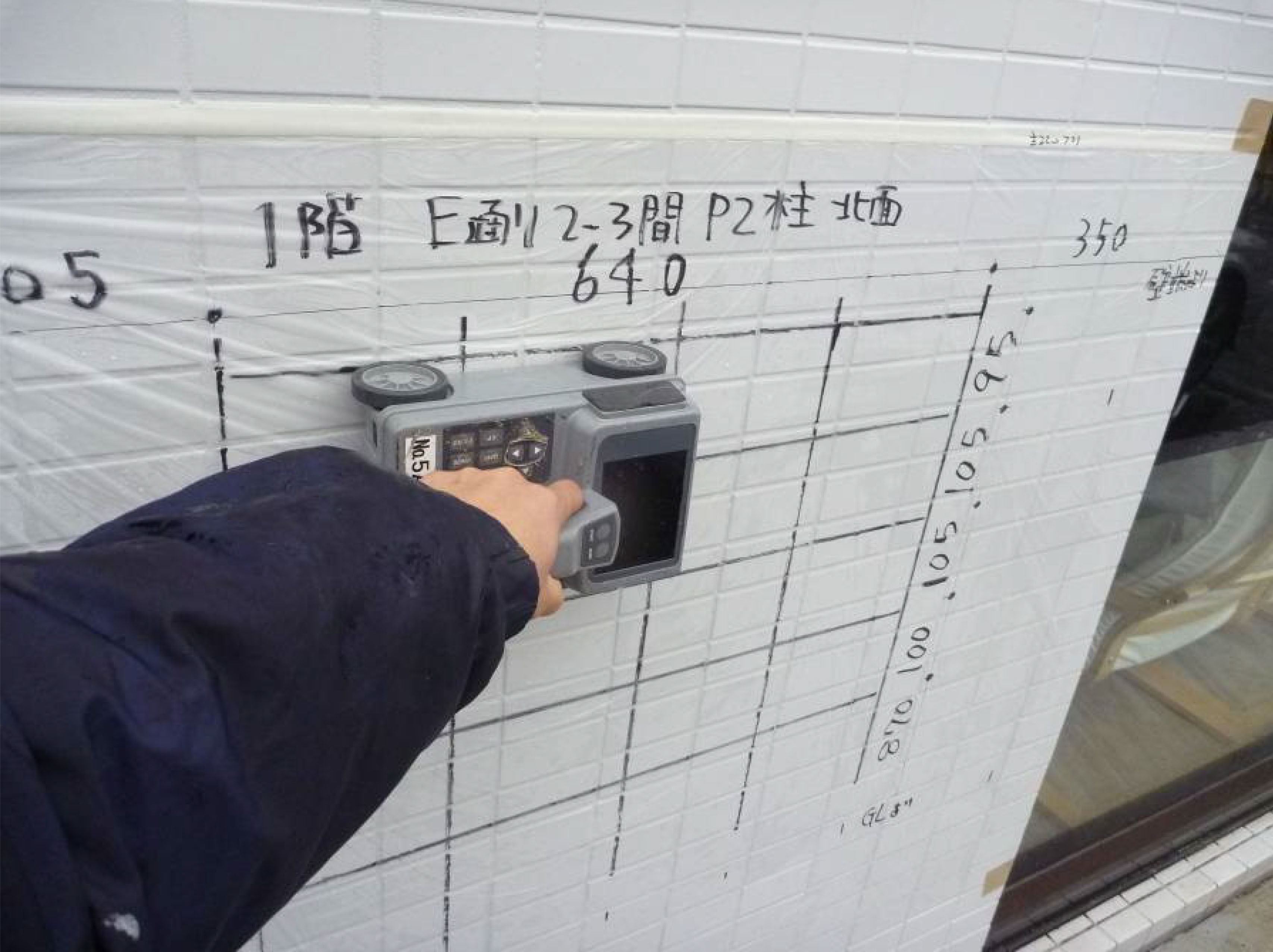 鉄筋探査機を用いて既存建物の構造調査を実施している現場写真