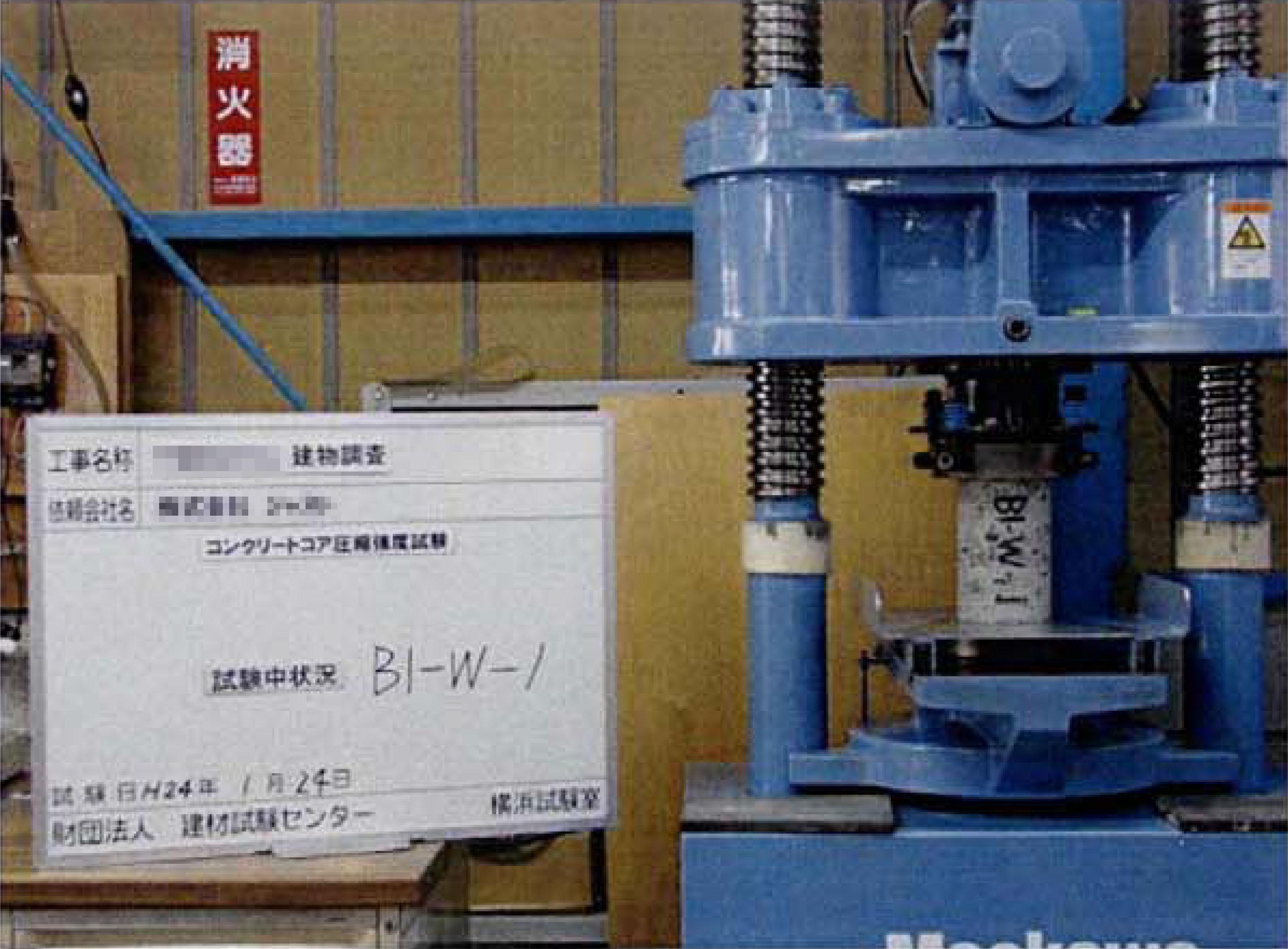 アムスラー試験機で供試体に荷重をかけているコンクリート強度試験の写真